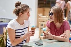 Le tir d'intérieur de jeunes amis féminins heureux regardent joyeux l'un l'autre, mangent la crème glacée, discutent quelque chos Photographie stock libre de droits