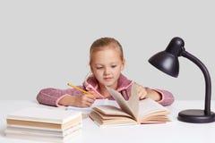 Le tir d'intérieur de la petite fille agréable à regarder porte les vêtements sport, se repose au bureau, allume le livre, fait l images libres de droits