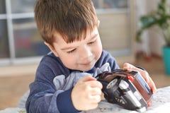 Le tir d'intérieur du petit enfant beau tient la voiture de jouet dans des mains, pose d'intérieur contre l'intérieur domestique  photographie stock libre de droits
