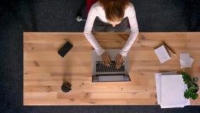 Le tir de chariot, complètent en bas de la vue de la femme de gingembre dactylographiant sur un ordinateur portable dans le burea banque de vidéos