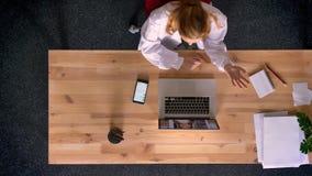 Le tir de chariot, complètent en bas de la vue de la femme de gingembre habillée dans le manteau de laboratoire parlant dans le v banque de vidéos