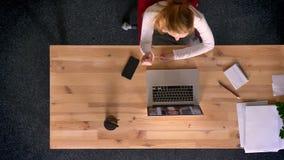 Le tir de chariot, complètent en bas de la vue de la femme de roux parlant dans le videochat utilisant l'ordinateur portable dans banque de vidéos