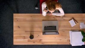 Le tir de chariot, complètent en bas de la vue de la femme de roux parlant sur le téléphone portable dans le bureau banque de vidéos