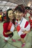 Le tir de Fisheye de la femelle deux avec le tatouage SG50 sur des visages, tiennent de mini drapeaux nationaux avec la fierté et Photos stock
