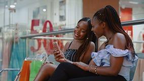 Le tir de glissière de deux filles font Selfie avec le téléphone après l'achat clips vidéos