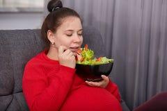 Le tir de la femme mignonne enceinte de brune attrayante a plaisir à manger de la salade fraîche des tomates et de la laitue, pos photographie stock