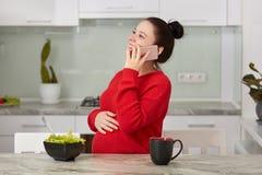 Le tir de la jeune femme de sourire attirante anticipe pour le bébé, garde la main sur le ventre, a la conversation téléphonique  photos stock