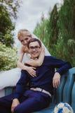 Le tir de mariage des jeunes mariés se reposent sur le banc en parc Photographie stock libre de droits