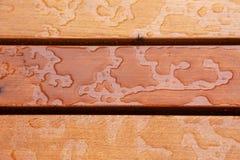 Le tir de plan rapproché de la pluie se laisse tomber sur un banc en bois brun photos libres de droits