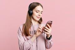 Le tir de studio de femal agréable à regarder lit des actualités en ligne sur le téléphone portable ou observe la vidéo dans des  Photo stock