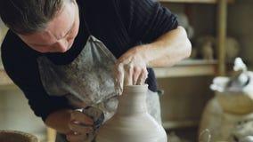 Le tir en gros plan des jeunes traînent le vase en céramique de moulage de l'argile sur la roue de lancement tout en travaillant  banque de vidéos