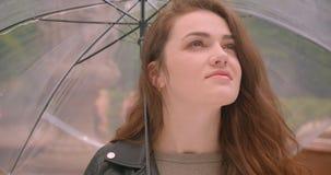 Le tir en gros plan du modèle caucasien de brune ouvre le parapluie prévoyant la pluie en parc pluvieux vert banque de vidéos