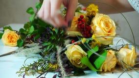 Le tir en gros plan du processus en tant que concepteur féminin de fleur apporte la touche finale à la composition florale à la t banque de vidéos