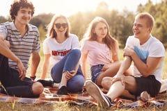 Le tir extérieur de jeunes amis heureux ont l'amusement ensemble, se reposent près de l'un l'autre, disent des anecdotes, appréci Photographie stock libre de droits