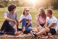 Le tir extérieur des quatre amis heureux ont l'amusement ensemble pendant le pique-nique d'été, dernières nouvelles de dicuss, pa Photographie stock