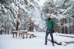 Le tir extérieur du mâle barbu beau habillé dans des vêtements chauds, a l'amusement pendant que la neige de jets en air, passe d image stock