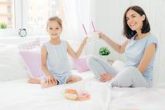 Le tir horizontal de joli femelle et sa fille font tinter des verres avec le cocktail dans le lit, prennent le petit déjeuner dan photos libres de droits