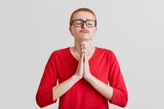 Le tir horizontal de la femme d'une chevelure rouge pleine d'espoir avec les yeux fermés, paumes de presses ensemble, a parler en Image stock