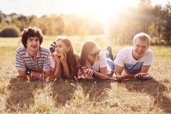 Le tir horizontal de quatre amis heureux se trouvent sur la terre, ont le pique-nique pendant le jour d'été ensoleillé, ont des e Photos stock