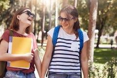 Le tir horizontal des amis heureux tiennent la main et ont des expressions joyeuses, habillées dans des vêtements sport, les sacs Photo stock