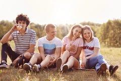 Le tir horizontal des quatre amis heureux se reposent sur la terre, ont des expressions heureuses, boivent de la limonade froide  Photographie stock libre de droits