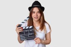 Le tir horizontal du beau jeune producteur cinématographique féminin choqué tient le bardeau de film, utilise le chapeau, T-shirt photos stock