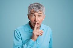 Le tir horizontal du mâle d'une chevelure gris regarde avec l'expression perplexe l'appareil-photo, garde le doigt antérieur sur  images libres de droits