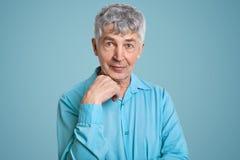 Le tir horizontal du retraité masculin caucasien d'une chevelure gris mûr utilise la chemise élégante, garde la main sous le ment photos libres de droits