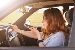 Le tir latéral de femelle concentré tourne roulent autour dedans la voiture, fait l'appel vocal par l'intermédiaire du téléphone  Image stock