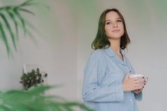 Le tir latéral de la femme caucasienne rêveuse s'est habillé dans des vêtements sport, boit du thé, se tient d'intérieur contre l photo libre de droits