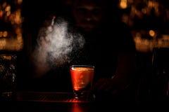 Le tir obscurci du barman verse un cocktail d'alcool utilisant le pulvérisateur photographie stock libre de droits