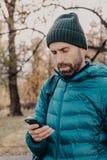 Le tir vertical du type concentré de hippie avec la barbe épaisse, utilise l'anorak et le chapeau, juge cellulaire, emploie l'app photos stock