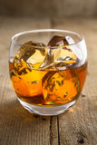 Le tir vertical du verre solitaire de bourbon de whiskey sur les roches glacent le bois repris par vintage photos libres de droits