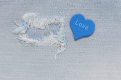 Le tissu de jeans déchiré avec un coeur bleu et un mot aiment Images stock