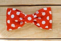 Le tissu de lien avec les points de polka rouges se trouvent sur un fond en bois Image stock