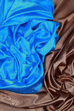 Le tissu en soie bleu et brun de satin des plis onduleux donnent au fond une consistance rugueuse Photo libre de droits