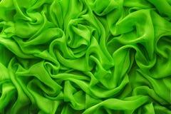 Le tissu ondule le fond, vague de tissu, vêtements verts de satin Image libre de droits