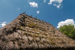 Le toit est couvert de paille contre le ciel bleu Image libre de droits