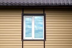 Le toit et le mur en métal de bâtiment ont fini avec les panneaux de voie de garage beiges avec la fenêtre en plastique blanche Images libres de droits