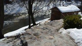 Le toit extérieur de bain public d'escaliers en pierre a couvert la rivière d'hiver de neige banque de vidéos