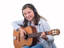 Le tonåringflickan som spelar den akustiska gitarren på vit arkivfoto