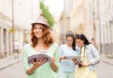 Le tonårs- flickor med den stadshandböcker och kameran Arkivfoto