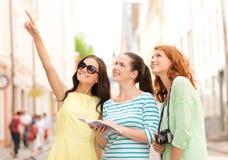 Le tonårs- flickor med den stadshandboken och kameran Fotografering för Bildbyråer