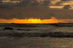Le tonalità arancio del tramonto hanno riflesso nelle onde Immagine Stock