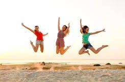 Le tonåriga flickor som hoppar på stranden Fotografering för Bildbyråer