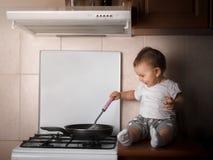 Le toodler de bébé préparant le dîner à la cuisine dans le riche foncé de poêle chauffent photos stock