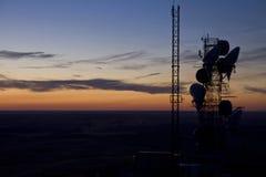 Le torri di microonda e delle telecomunicazioni silhoutted al crepuscolo, orientale Fotografia Stock Libera da Diritti