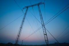 Le torri di potere ad alta tensione della fonte di forma del portone di calcio ai sunris Fotografia Stock