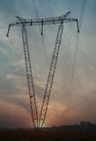 Le torri di potere ad alta tensione della fonte di V ad alba Fotografie Stock
