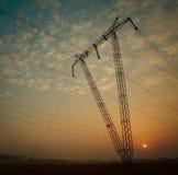 Le torri di potere ad alta tensione della fonte di V ad alba Immagine Stock